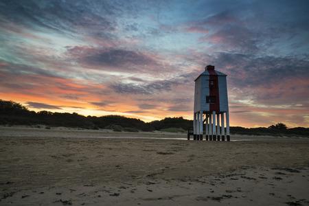 burnham: Stunning landscape sunrise stilt lighthouse on beach Stock Photo