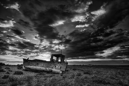 beach shingle: Barca da pesca abbandonata sulla spiaggia ghiaiosa paesaggio al tramonto in bianco e nero Archivio Fotografico