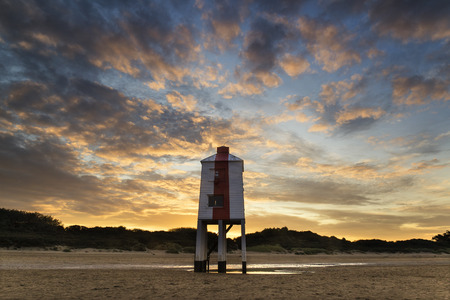 Stunning landscape sunrise stilt lighthouse on beach photo