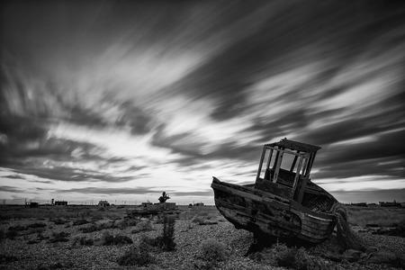 Abandoned fishing boat on shingle beach landscape at sunset black and white photo
