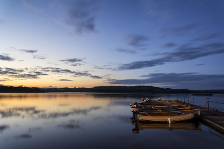 Landscape sunrise over still lake with boats on jetty photo