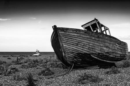 beach shingle: Peschereccio abbandonato sulla spiaggia ghiaiosa paesaggio al tramonto in bianco e nero