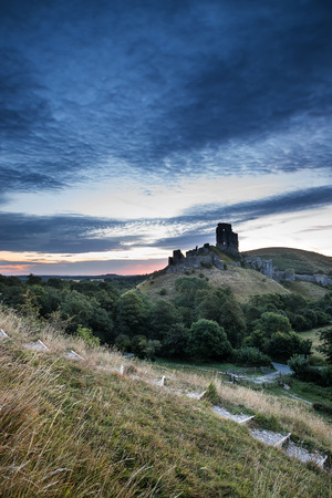 Stunning sunrise landscape over ruins of medieval castle photo