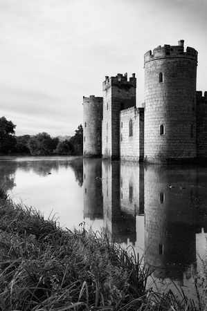 Beautiful medieval castle and moat at sunrise with mist over moat and sunlight behind castle black and white