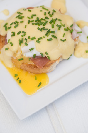 Eggs Benedict toasted English muffins ham poached eggs and delicious buttery hollandaise sauce photo