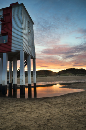 Stunning landscape sunrise stilt lighthouse on beach Stock Photo