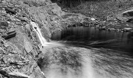 Landscape image of waterfall flowing into old abandoned quarry black and white photo