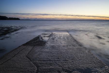 slipway: Long exposure landscape image of pier at sunset