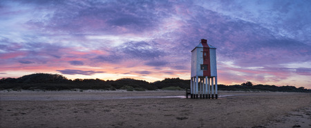 Beautiful sunrise over lighthouse on beach landscape Stock Photo
