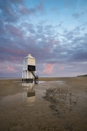 burnham: Stunning landscape sunrise stilt lighthouse on beach Stock Photo