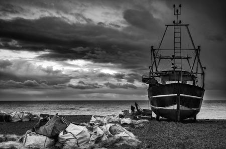 beach shingle: Barca da pesca sulla spiaggia di ciottoli paesaggio con cielo tempestoso in bianco e nero