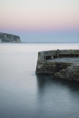 Long exposure landscape of stone jetty in calm seas photo
