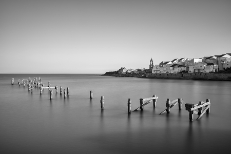 Beautiful calming long exposure landscape of ruined pier at sunset photo