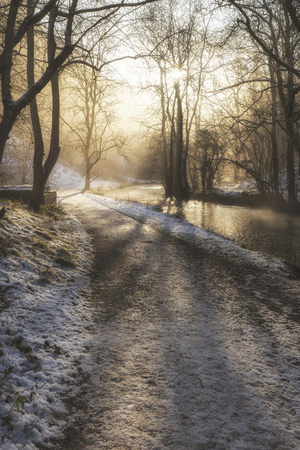 Beautiful Winter snow covered countryside landscape of river flowing with reflections photo
