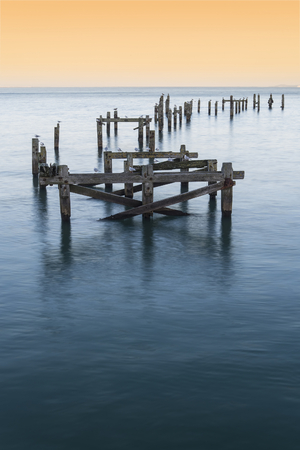 calming: Beautiful calming long exposure landscape of ruined pier at sunset