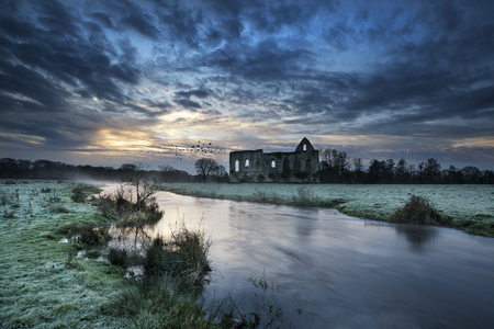 Beautiful dawn landscape of Priory ruins in countryside location photo