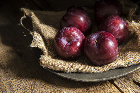 Fresh plums on sack and vintage plate