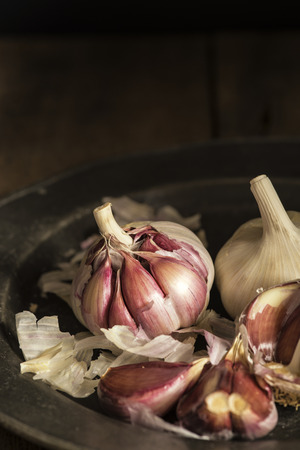 Fresh garlic cloves in moody natural lighting set up with vintage style