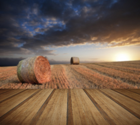 hay bales: Lovely sunset golden hour landscape of hay bales in field in English countryside with wooden planks floor Stock Photo