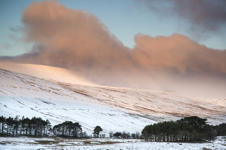 brecon beacons: Stunning pink sunrise over mountain Winter landscape