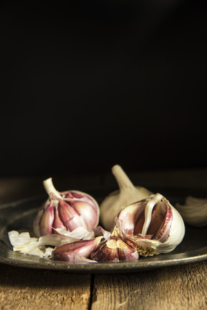 natural  moody: Fresh garlic cloves in moody natural lighting set up with vintage style