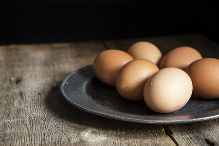 pewter: Fresh eggs on pewter plate in vintage style natural lighting set up