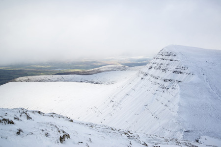 brecon beacons: Stunning landscape views from top of deep snow covered mountains in Winter in cloud inversion