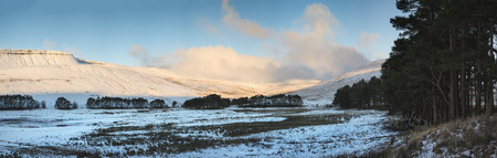 brecon beacons: Beautiful panorama of Winter landscape with snow covered montain range and forest Stock Photo