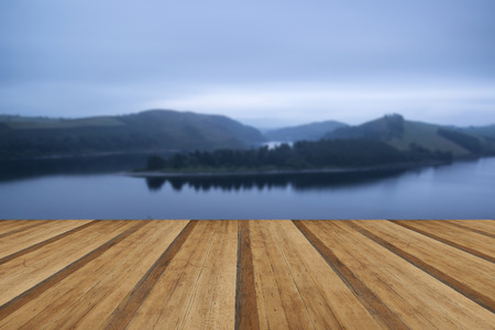 Moody landscape image of lake pre-dawn in Autumn with wooden planks floor