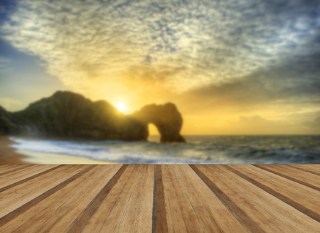 Beautiful sunrise over ocean with rock stack in foreground with wooden planks floor photo