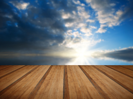 Stunning landscape at sunset reflected in ocean with wooden planks floor Stock Photo