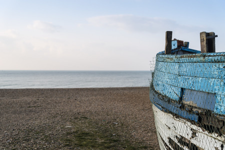 flaking: Old abandoned fishing boat on beach with shallow depth of field
