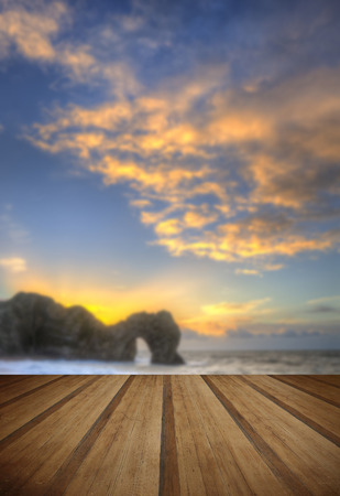 Winter sunrise at Durdle Door on Jurassic Coast in England with wooden planks floor photo
