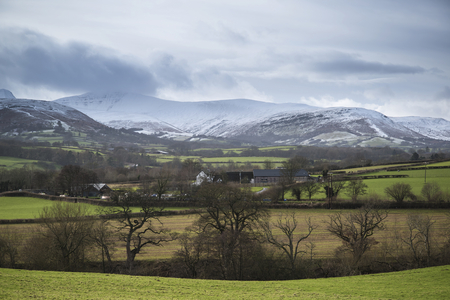 snow covered mountain: Countryside landscape with snow covered mountain range in distance