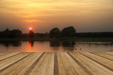 nautral: Beautiful simple image of sunset through tress reflected in lake in foreground with wooden planks floor Stock Photo