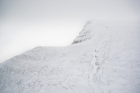 inversion: Stunning landscape views from top of deep snow covered mountains in Winter in cloud inversion