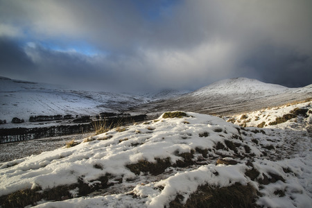 brecon beacons: Beautiful landscape of snow covered mountain range during late afternoon in Winter Stock Photo