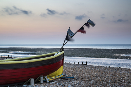 spring tide: Landscape image of small fishing boats on beach at sunrise