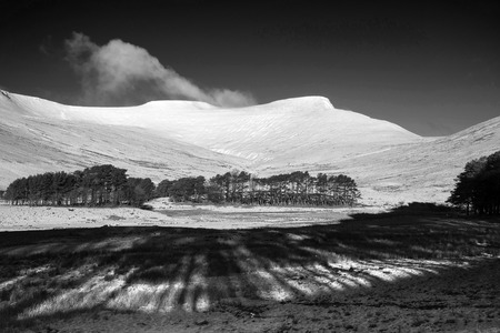 brecon beacons: Fresh Winter landscape of mountain range covered in snow black and white Stock Photo