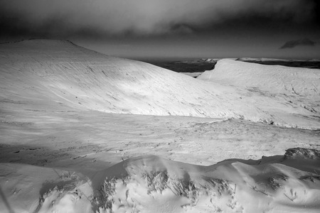 brecon beacons: Stunning landscapeof snow covered mountains in Winter in black and white