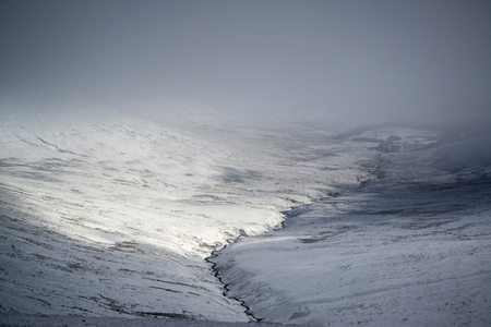 Moody dramatic low cloud Winter landscape in mountains with snow on ground