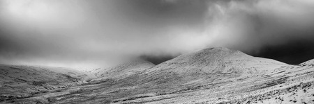 of pano: Stunning Winter panorama landscape snow covered mountains in black and white