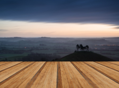 valley below: Beautiful sunrise dawn landscape of countryside overlooking brightly lit town in valley below with wooden planks floor Stock Photo