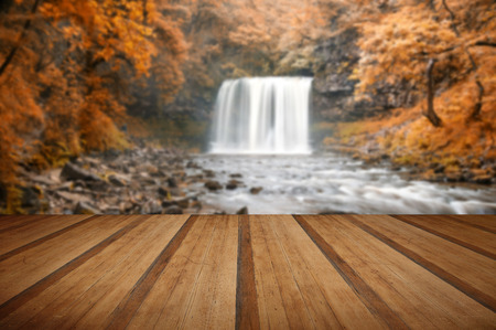 natual: Beautiful image of waterfall in forest with stram and lush Autumn Fall foliage with wooden planks floor Stock Photo