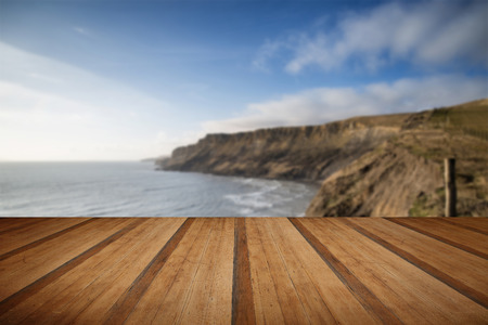 Cliffs landscape stretching out to sea in Summer with wooden planks floor Stock Photo