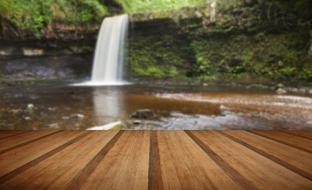 copse: Beautiful image of waterfall in forest with stram and lush green foliage with wooden planks floor Stock Photo