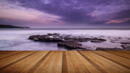 kimmeridge: Stunning toned landscape seascape coastline and rocky shore at sunset with wooden planks floor Stock Photo