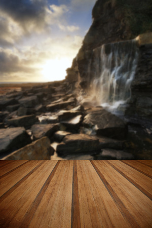 Beautiful landscape waterfall flowing into rocks on beach at sunset with wooden planks floor