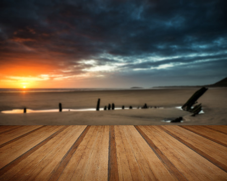 helvetia: Dramatic sunset landscape over shipwreck on Rhosilli Bay beach with wooden planks floor Stock Photo