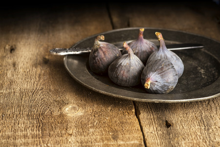 Fresh figs in moody natural lighting set with vintage style Stock Photo